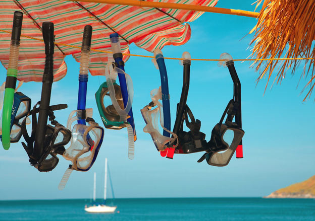 snorkel masks hanging to dry at the beach