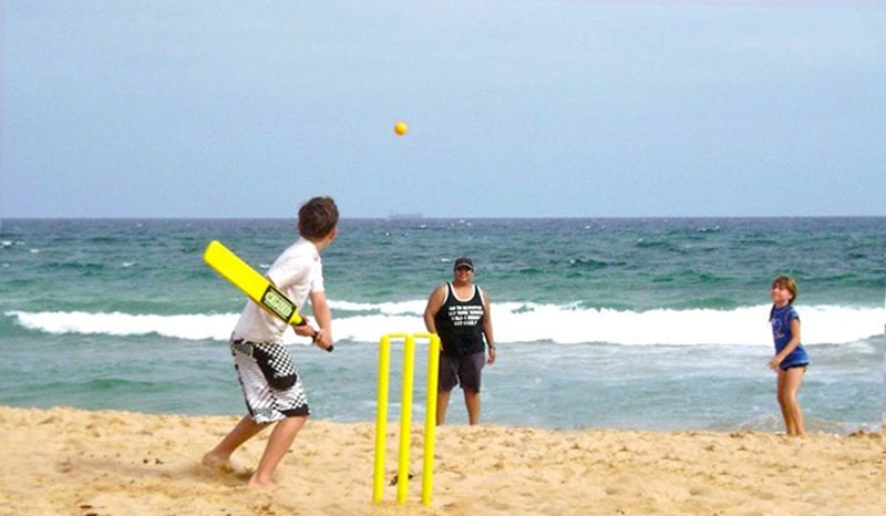 family playing beach cricket at the beach