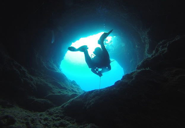 man diving out of a cave