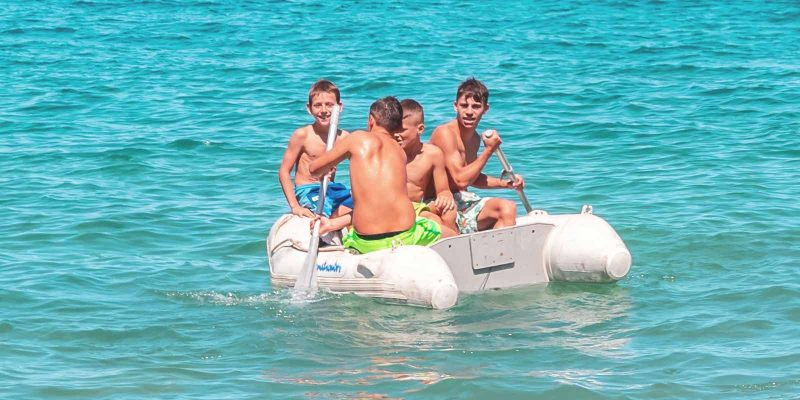 four boys in an nflatable boat